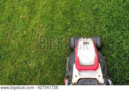 Part Of Lawn Mover On Green Grass In Modern Garden. Garden And Backyard Landscape Lawnmower. Garden