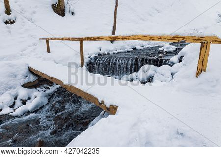 Wooden Bridge Over A Mountain Stream In A Forest Valley In The Carpathian Mountains