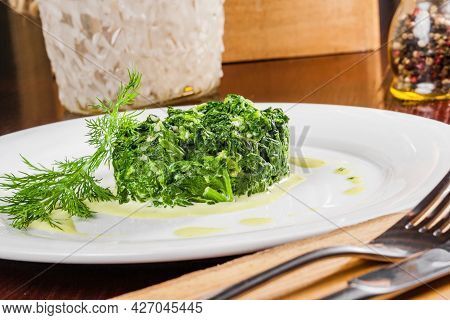 Cooked Spinach With Garlic On A White Plate. Vegetarian Food.