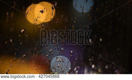 Drops Of Night Rain On Dirty Glass Window With Golden Purple Bokeh Lights Of City Traffic. Rainy Wea