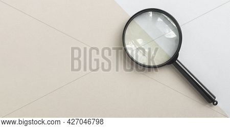 Magnifying Glass Or Loupe On Pale Blue And Beige Background. Magnifier Banner With Copy Space.