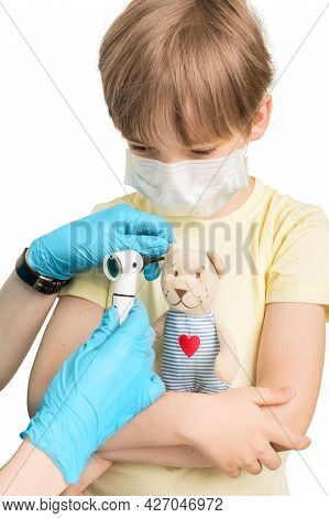 Caucasian Boy With A Toy In His Hands. The Doctor Conducts Ear Swing Of The Ears Of A Toy Bear. Appo