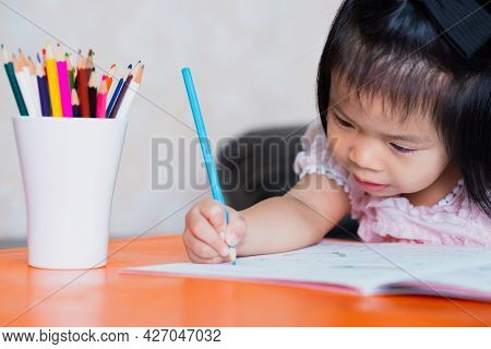 A 4-5 Year Old Child Girl Is Having Fun Coloring In Blue Pencils In Her Workbook.