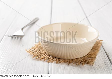 Empty Beige Bowl And Metal Fork On A White Wooden Table. Clean Porcelain Soup Bowl On A Table. Empty