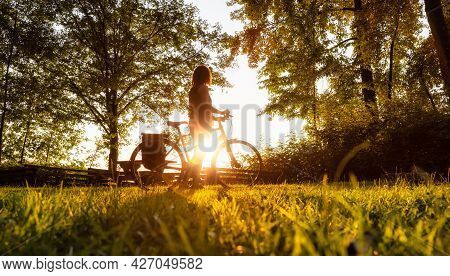 Adventurous White Cacasusian Woman With A Bicycle In A Park. Sunny Summer Sunset. Barnston Island, V