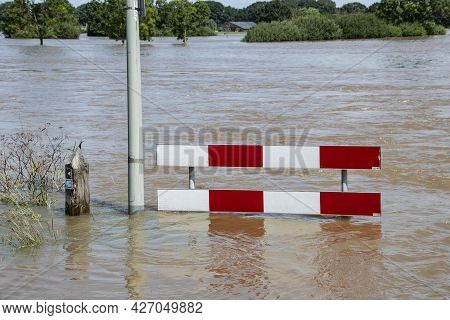 Flooded Street After Recent Rains. Warning Signs Up To Prepare Drivers For Possibly Water Damage To