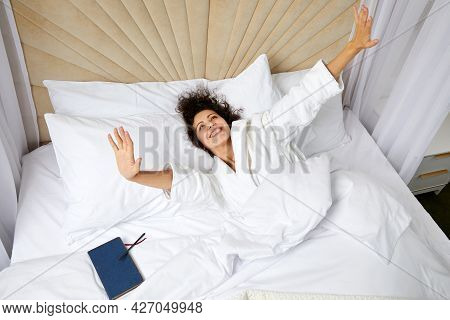 Young Smiling Woman Waking Up In Bed And Stretching Her Arms Up, Concept Of Happy Beginning Of The D