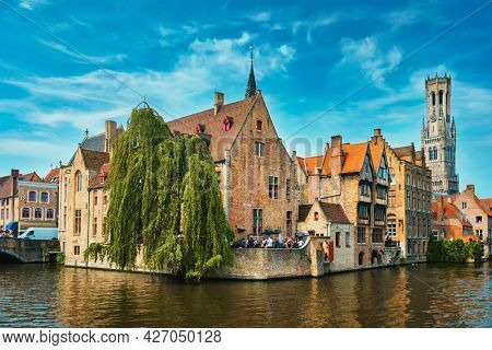 Famous view of Bruges tourist landmark attraction - Rozenhoedkaai canal with Belfry and old houses along canal with tree. Brugge, Belgium