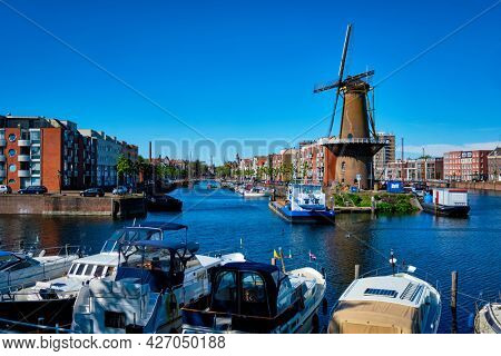 View of the harbour of Delfshaven with the old grain mill known as De Destilleerketel. Rotterdam, Netherlands