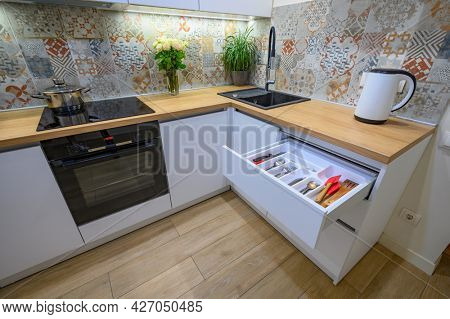 Closeup view to small compact and cozy white modern kitchen interior, drawer pulled out, low angle view
