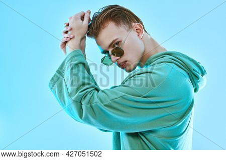 Handsome young man poses in trendy sweatshirt and sunglasses on a blue background. Glasses fashion. Studio portrait.