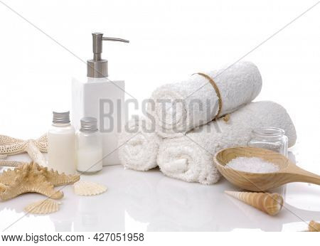 Skin care SPA concept with orchid and rolled towel, oil bottle, shell candle,on white background