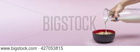 Cooking Muesli. A Woman Pours Milk From A Jug Into A Saucer With Muesli Flakes. Pink Background With
