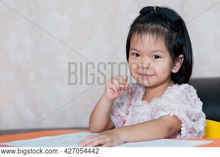 Cheerful Girl With White Pencil Touching Her Cheek. Child Sweet Smiling. Kid Sitting At The Table. H
