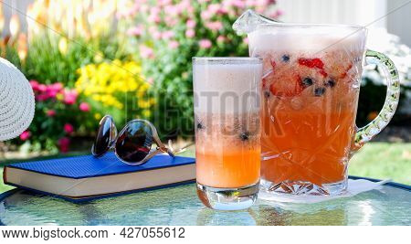 Strawberry Lemonade In A Glass And Pitcher With A Book, Sun Glasses, And A Hat On A Shady Backyard P