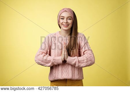 Please Do Me Favour. Charming Young Female Student Wearing Knitted Sweater, Headband Pressing Palms
