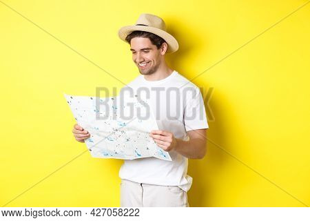Travelling, Vacation And Tourism Concept. Smiling Happy Tourist Looking At Map With Sightseeings, St