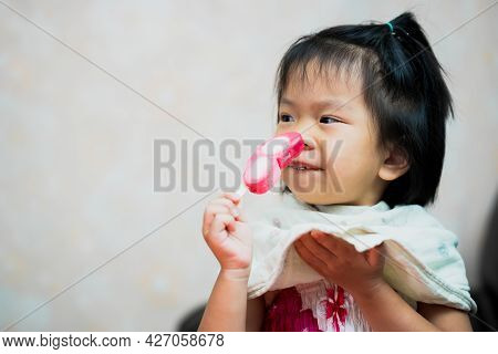 Asian Child Girl Eating Pink And White Sweet Popsicle. Kid Use Hand-held Apron To Support The Melted