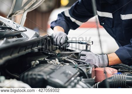 Mechanic Works On The Engine Of The Car In The Garage. Repair Service. Concept Of Car Inspection Ser
