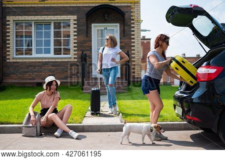 Three Caucasian Women And A Dog Are Going On A Road Trip. The Girls Are Loading Their Suitcases Into