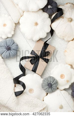 Stylish Flat Lay With Uxury Paper Craft Gift Box And Black Satin Ribbon Bow On Natural Pumpkin Squas