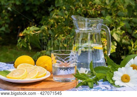 In A Glass Jug, Pure Refreshing Water With Lemon And Mint To Quench Your Thirst.