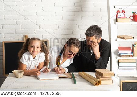 Dad Teaching Schoolchild Girls. Father And School Kids Daughters At School. Reading Book And Writing