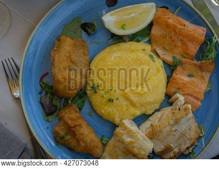 Image Of Assorted Fried Fish With Polenta On A Blue Plate