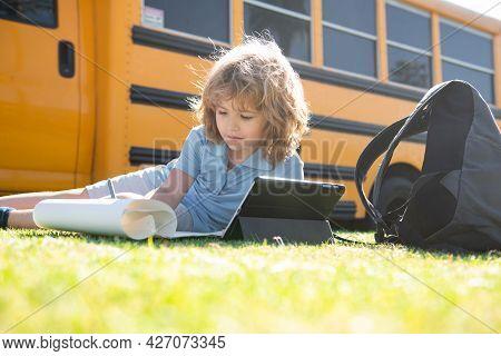 Back To School. Happy Child Study In Park Near School Bus. Schoolboy Doing Homework Or Online Educat