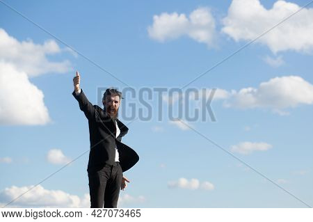 Man In Suit Hand Raising On Sky Background. Freedom Adventure And Business Victory Concept. Success