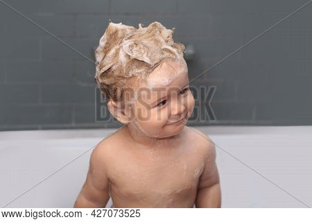Funny Baby Kid Bathed In Foam And Washing In Bathtub At Home. Kid Bathing In Bathtub.