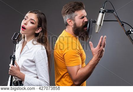 Singer Duet Couple Is Performing A Song With A Microphone While Recording In A Music Studio.
