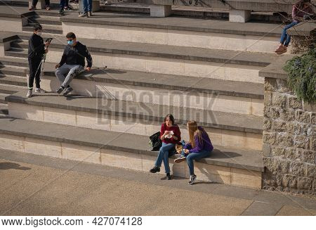 Young People In Masks Having A Rest On The Steps Of The Square In Viterbo, Italy