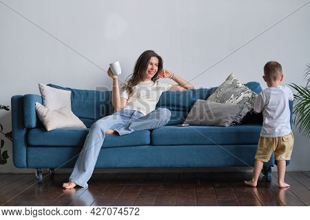 Tired Young Mother Or Nanny Sits On The Couch And Watches Her Son Playing.