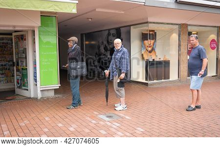 Bonn, Germany - July 30, 2021, Men In Line At A Pharmacy Wearing Masks And Without Masks During The