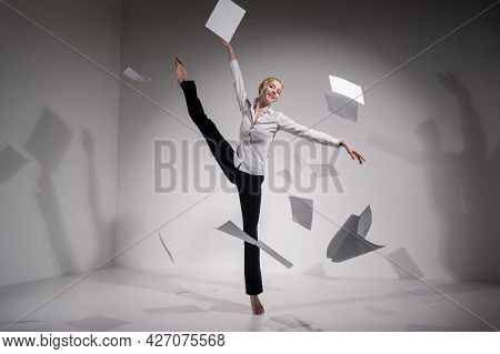 A Graceful Ballerina In A Business Suit Throws Documents In The Studio. Business Woman Dance Barefoo