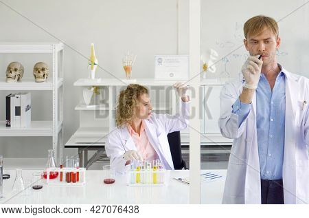 Young Brazilian Scientist Write Chemical Formulas On The Glass Board. Young Blonde Assistant Looking