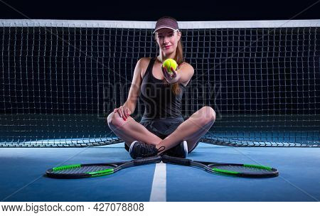 Portrait Of A Beautiful Tennis Player Sitting On The Court. Sports Concept.