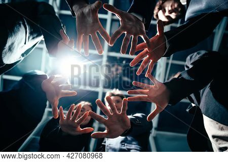 Close Up. Group Of Young Business People Joining Their Palms In A Circle.