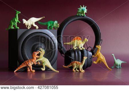 Toy Dinosaurs Next To An Audio Speaker And Headphones. The Concept Of Children's Audio Tales And Edu