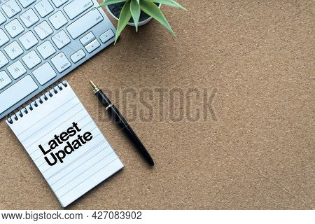 Latest Update Text With Notepad, Decorative Plant, Keyboard And Fountain Pen On Wooden Background. B