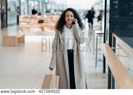 Young Woman With A Shopping Bag Talking On A Smartphone .