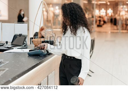Young Woman With A Smartphone Standing In A Supermarket Coffee Shop.