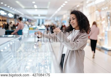 Young Woman Choosing A Piece Of Jewelry In A Jewelry Store.