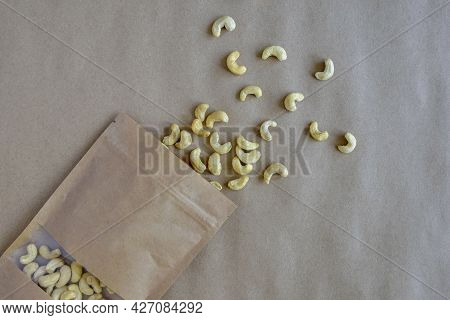 Cashew Nuts In Eco-friendly Paper Packaging And On Kraft Paper. Healthy Food. Top View. Close-up. Se