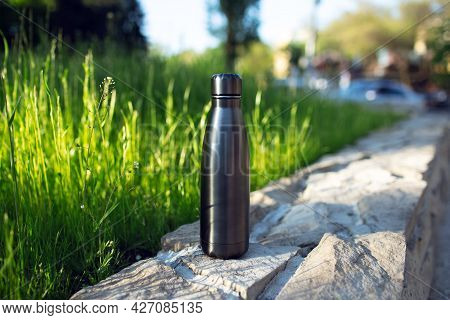 Stainless Thermo Water Bottle Of Black On Background Of Green Grass. Reusable Bottles; Zero Waste; E