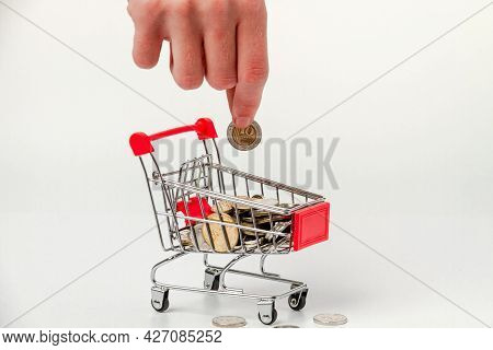 A Man's Hand Puts 10 Israeli Shekels Into A Grocery Cart Containing Israeli Coins.