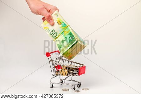 A Man's Hand Puts A Stack Of 50 Israeli Shekels Into A Grocery Cart Filled With Israeli Coins.
