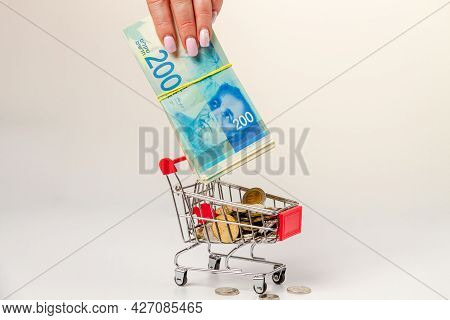 A Woman's Hand Puts A Stack Of 200 Israeli Shekels Into A Grocery Cart Filled With Israeli Coins.