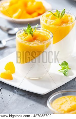 Glass Of Homemade Panna Cotta With Mango Sauce